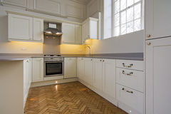 Contemporary fully fitted kitchen in beige Stock Photo