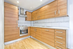 Contemporary fully fitted wooden kitchen. With silver appliances and massive work space stock photo