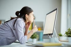 Contemporary Girl Using Computer. Side view portrait of contemporary young woman looking at computer screen while working in office, copy space stock photos