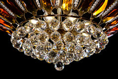 Contemporary gold chandelier isolated on black background. Crystal chandelier decorated amber crystals close-up Stock Images