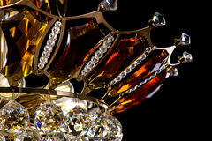 Contemporary gold chandelier isolated on black background. Crystal chandelier decorated amber crystals close-up Stock Photos