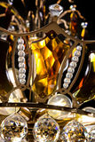 Contemporary gold chandelier isolated on black background. Crystal chandelier decorated amber crystals close-up Royalty Free Stock Image