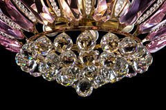 Contemporary gold chandelier isolated on black background. Crystal chandelier decorated Pink crystals close-up Stock Photos