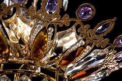 Contemporary gold chandelier isolated on black background. Crystal chandelier decorated purple crystals close-up Stock Photos
