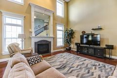 Contemporary great room with fireplace and built-in mirror. Elegant home with staged decor and staircase stock image