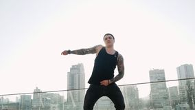 Contemporary hip hop street dancer hipster man with tattoo funky urban dancing freestyle in the city. 4k slow motion stock footage