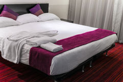 Contemporary hotel room suite queen size bed. Red carpet Royalty Free Stock Images