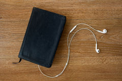 Contemporary image of a Bible with headphones. Royalty Free Stock Image