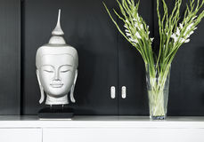 Contemporary interior design detail. With buddhist statue and flowers Stock Photos