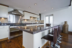 Contemporary kitchen with a breakfast bar. And polished stone work top Royalty Free Stock Photos