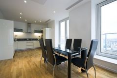 Contemporary kitchen and dining area. Contemporary fully fitted kitchen in white with dining area and large dining table for six Royalty Free Stock Photo