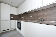 Contemporary kitchen with natural stone worktop and tiles in whi. Contemporary fully fitted kitchen in white with modern chrome appliances and natural stone Stock Images