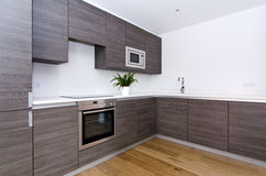 Contemporary kitchen with top spec appliances. Contemporary modern fully fitted kitchen in brown with top spec appliances and granite worktops Stock Photography