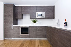Contemporary kitchen with top spec appliances. Contemporary modern fully fitted kitchen in brown with top spec appliances and granite worktops royalty free stock image