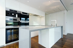 Contemporary kitchen with top spec appliances. Contemporary modern fully fitted kitchen in white with top spec appliances and granite worktops Stock Image