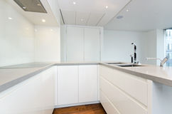 Contemporary kitchen with top spec appliances. Contemporary modern fully fitted kitchen in white with top spec appliances and granite worktops royalty free stock image