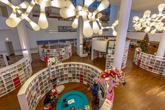 Contemporary library interior. AMSTERDAM, NETHERLANDS - DECEMBER 29, 2016: Interior of a modern library with bent bookshelfs and funny lighting in the royalty free stock photography
