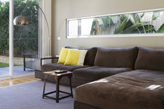 Contemporary lounge sofa interior. Contemporary lounge with outlook to garden and coffee table and lamp Royalty Free Stock Images