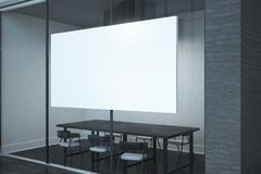 Contemporary meeting room with billboard. Contemporary meeting room with empty billboard on glass wall. Presentation concept. Mock up, 3D Rendering Royalty Free Stock Images