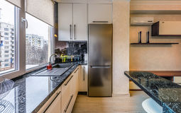 Contemporary modern black colored kitchen. With fitted appliances and breakfast bar, window view on buildings at chisinau albisoara street, moldova Stock Photos