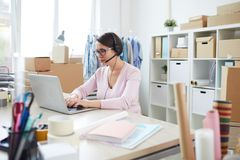 Contemporary online shop manager in headset chatting with clients. Contemporary online shop manager in headset typing on laptop keypad while chatting with stock images