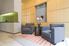 Contemporary open plan hallway. Contemporary open plan reception or hallway with designer armchairs and display show glass cabinet Stock Images