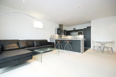 Contemporary open plan living room with kitchen. Dining bar, dining area and large black leather sofa Stock Photos
