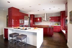 Contemporary red modern kitchen with 2 different island. And a dark wooden floor royalty free stock images
