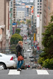 Contemporary Scene Of San Francisco As Woman Crosses Hilly Street Royalty Free Stock Photos