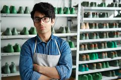 Young cobbler. Contemporary self-employed shoemaker in his workshop stock image