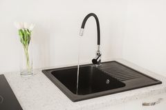 Contemporary sink with tap in the luxury kitchen. White luxury furniture. New black open faucet. Modern apartment. Water flow from. The tap in the kitchen. Open stock photo