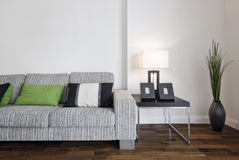 Contemporary sofa. Large contemporary designer sofa with side table and reading lamp Royalty Free Stock Images