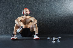 Contemporary Sportsman on Floor Resting after Gym Workout Royalty Free Stock Photography
