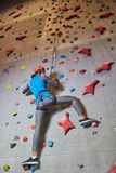 Climbing upwards. Contemporary sportsman in helmet and activewear holding by rope while moving upwards along climbing wall Royalty Free Stock Photo