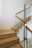 Contemporary stair case. With wooden steps and glass rails Royalty Free Stock Photo