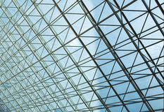 Contemporary steel structure and transparent glass roof. Revealing blue sky with light clouds Stock Image