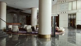 Contemporary-styled lounge in five-star hotel. Corporate design. Main hall of a luxury hotel with a dark marble floor and opaline columns equipped with a modern