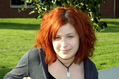 Contemporary Teen. Portrait of a teenage girl sitting outside on school grounds stock image