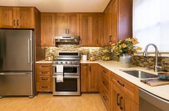 Contemporary upscale home kitchen interior with cherry wood cabinets, quartz countertops, sustainable recycled linoleum floors & stock photo