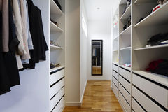 Contemporary walk in wardrobe. Contemporary spacious walk in wardrobe in a modern home Royalty Free Stock Images