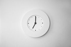 Contemporary white clock on the wall. Contemporary minimalist white clock on a plastered white wall Royalty Free Stock Photography