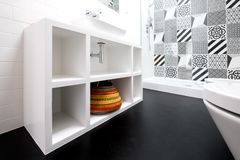 Contemporary white painted MDF bathroom unit, with colourful basket and black vinyl flooring