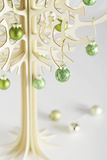Contemporary wooden christmas tree green balls. Small stylized wooden christmas tree made from bolser wood with green baubles Royalty Free Stock Image