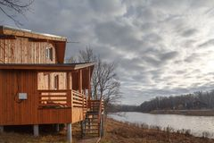 Contemporary wooden single family cottage on lake stock photos