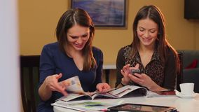 Contemporary young adult ladies in cafe reading magazines chat. Stock footage stock footage