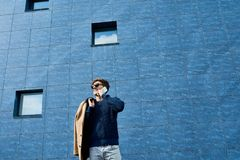 Contemporary Young Man Speaking by Phone Outdoors. Low angle portrait of handsome young man wearing sunglasses speaking by phone and smiling happily standing in Royalty Free Stock Photo