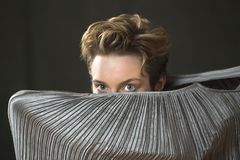 Young woman in silver dress dancing in the studio. Contemporary young woman dancer with short hair, immersed in a silver bag dress, peering out with only her Royalty Free Stock Photo