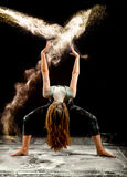 Contemporary dance flour jump. Expressive dance movement of a woman contemporary ballet dancer on stage with a black background throwing white powder stock image