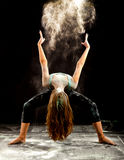 Contemporary dance powder. Expressive dance movement of a female contemporary ballet dancer on stage with a black background throwing white flour Royalty Free Stock Photography