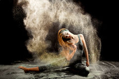 Contemporary dancer flour. Expressive dance movement of a female contemporary ballet dancer on stage with a black background throwing white powder Royalty Free Stock Images